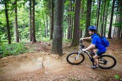 Adolescente biking en rastros del bosque Fotografía de archivo