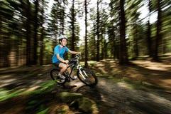 Adolescente biking en rastros del bosque Foto de archivo