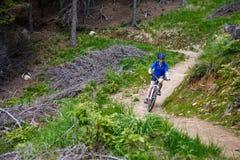 Adolescente biking en rastros del bosque Imagenes de archivo