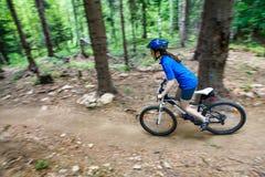 Adolescente biking en rastros del bosque Imagen de archivo