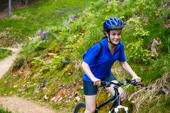 Adolescente biking en rastros del bosque Imágenes de archivo libres de regalías