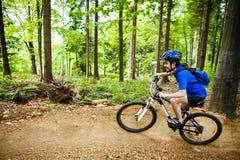 Adolescente biking en rastros del bosque Foto de archivo libre de regalías