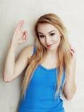 Adolescente biondo della donna che mostra il segno giusto della mano di successo Fotografie Stock