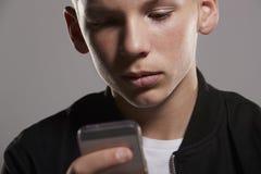 Adolescente blanco que consume el teléfono móvil, cierre, horizontal Imagen de archivo libre de regalías