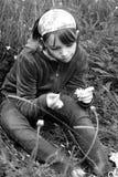 Adolescente blanco que cuenta los pétalos en hierba Foto de archivo libre de regalías