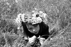 Adolescente blanco que cuenta los pétalos en hierba Fotografía de archivo