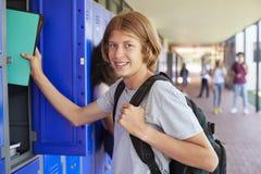 Adolescente blanco que usa el armario en pasillo de la escuela Imagen de archivo libre de regalías
