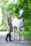 Adolescente blondy bastante joven con su caballo blanco preferido Foto de archivo