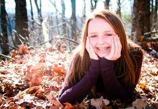 Adolescente bonito afuera en hojas Fotos de archivo libres de regalías