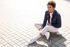 Adolescente bonito alegre que se sienta en calle Imagen de archivo libre de regalías