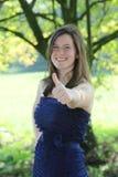 Adolescente bonito com a doação longa encaracolado bonita do cabelo polegares acima fotografia de stock