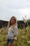 Adolescente bonito con el pelo rubio largo que se coloca en un campo de Imágenes de archivo libres de regalías