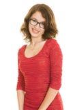Adolescente bonito con los apoyos en la sonrisa roja del vestido Foto de archivo libre de regalías
