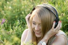Adolescente bonito con los auriculares en la hierba Imagen de archivo libre de regalías