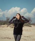 Adolescente bonito con los auriculares que escucha la música Imágenes de archivo libres de regalías