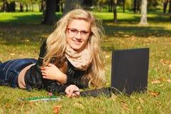 Adolescente bonito con una computadora portátil Foto de archivo