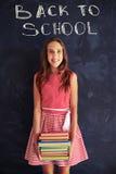 Adolescente bonito con una pila de libros listos para la nueva escuela YE Imagen de archivo libre de regalías