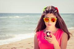 Adolescente bonito en gafas de sol y en un vestido rosado en un beac Imagen de archivo