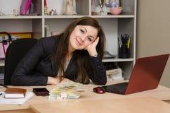 Adolescente bonito en la oficina con un paquete de billetes de banco Fotografía de archivo libre de regalías