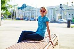 Adolescente bonito en ropa casual y gafas de sol que se sientan encendido Fotografía de archivo libre de regalías