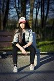 Adolescente bonito en un banco Foto de archivo libre de regalías