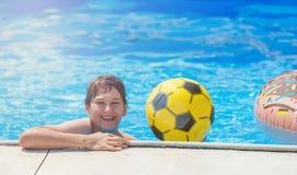 Adolescente bonito feliz do rapaz pequeno na piscina Jogos ativos na água, férias, conceito dos feriados Filhós do chocolate fotos de stock