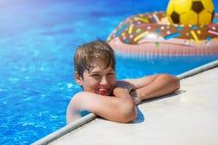 Adolescente bonito feliz do rapaz pequeno na piscina Jogos ativos na água, férias, conceito dos feriados Filhós do chocolate foto de stock