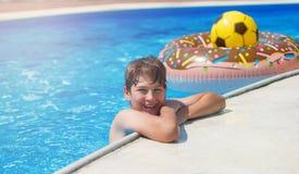 Adolescente bonito feliz do rapaz pequeno na piscina Jogos ativos na água, férias, conceito dos feriados Filhós do chocolate fotografia de stock