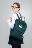Adolescente bonito feliz en vidrios con la mochila que mira detrás Fotografía de archivo libre de regalías