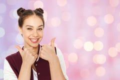 Adolescente bonito feliz que muestra los pulgares para arriba Foto de archivo