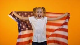 Adolescente bonito feliz que salta con la bandera americana, animando para el equipo preferido almacen de metraje de vídeo