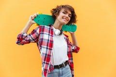 Adolescente bonito feliz que sostiene el monopatín en sus hombros Fotografía de archivo