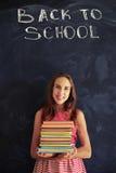 Adolescente bonito feliz sobre conseguir los nuevos libros de escuela para otros Foto de archivo libre de regalías