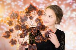 Adolescente bonito joven con las hojas de otoño Foto de archivo