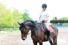 Adolescente bonito joven que monta un caballo en la escuela ecuestre Imágenes de archivo libres de regalías