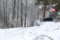 Adolescente bonito pequeno da menina que sledding em uma floresta ensolarada do inverno imagens de stock royalty free