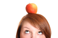 Adolescente bonito que balancea una manzana en su cabeza Fotografía de archivo libre de regalías