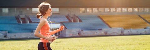 Adolescente bonito que corre no estádio, bandeira panorâmico imagens de stock