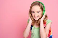 Adolescente bonito que disfruta de música en los auriculares Fotografía de archivo