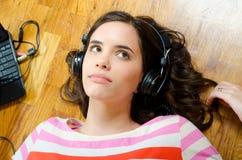 Adolescente bonito que escuta a música do caderno fotos de stock
