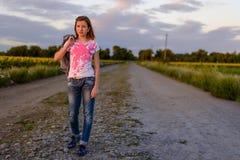 Adolescente bonito que espera en un camino rural en la puesta del sol Imágenes de archivo libres de regalías