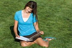 Adolescente bonito que estudia en la hierba Imagenes de archivo