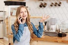 Adolescente bonito que habla en el teléfono en el trabajo Imagen de archivo libre de regalías