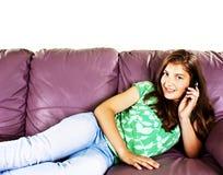 Adolescente bonito que habla en el teléfono, mintiendo en el sofá Imágenes de archivo libres de regalías