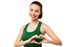 Adolescente bonito que hace símbolo del corazón con las manos Imagen de archivo libre de regalías