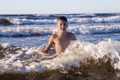 Adolescente bonito que juega en las ondas espumosas del mar Báltico Foto de archivo