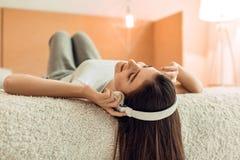 Adolescente bonito que miente en cama y que escucha la música Imagen de archivo