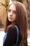 Adolescente bonito que mira hacia arriba en un ajuste al aire libre Imagen de archivo libre de regalías