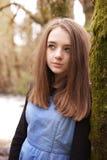 Adolescente bonito que mira hacia arriba mientras que se inclina contra un árbol Imagen de archivo