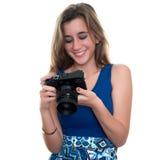 Adolescente bonito que mira imágenes en la exhibición posterior de a Imagenes de archivo